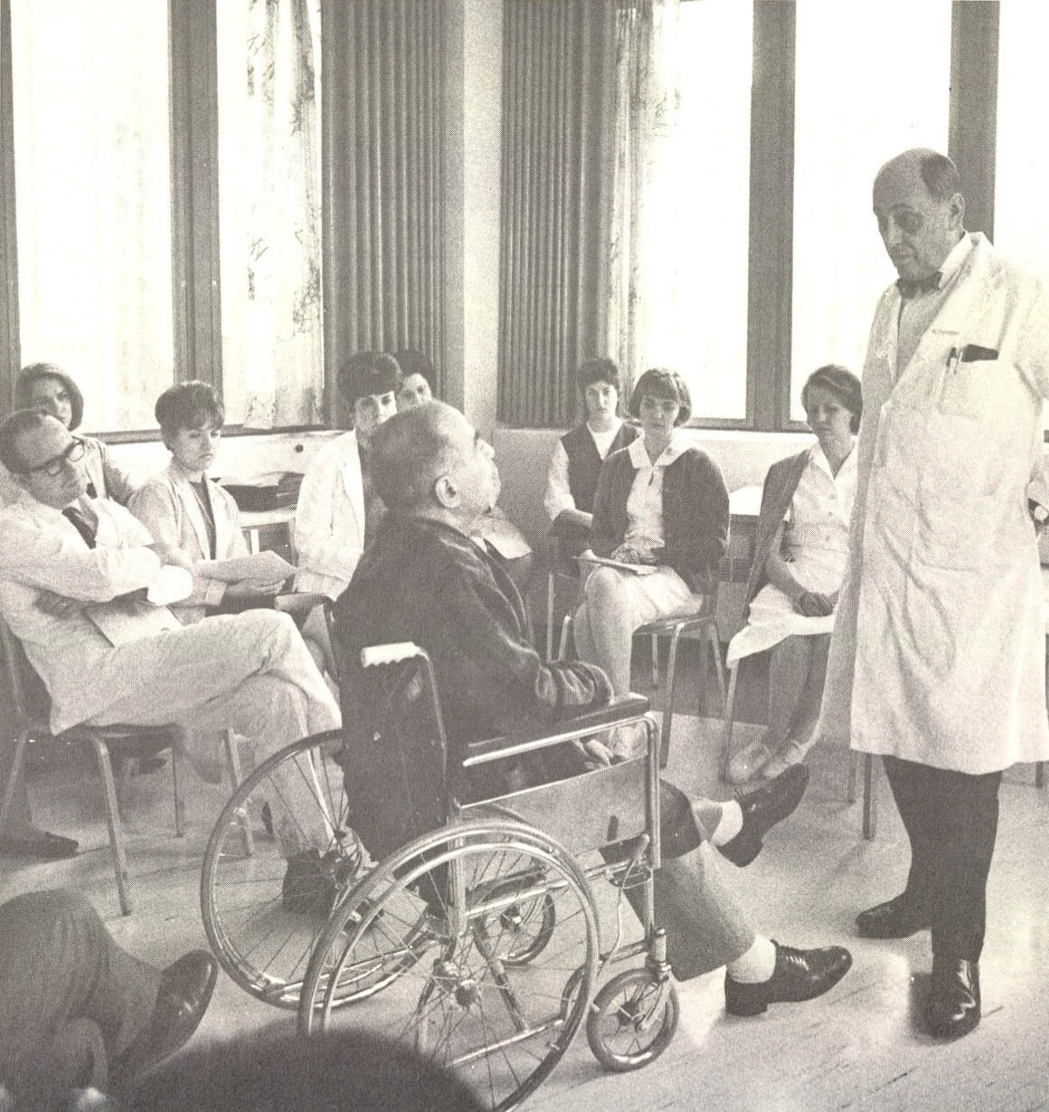 Historic photo of Rehabilitation Medicine department. A group of doctors and nurses examine a patient in a wheelchair
