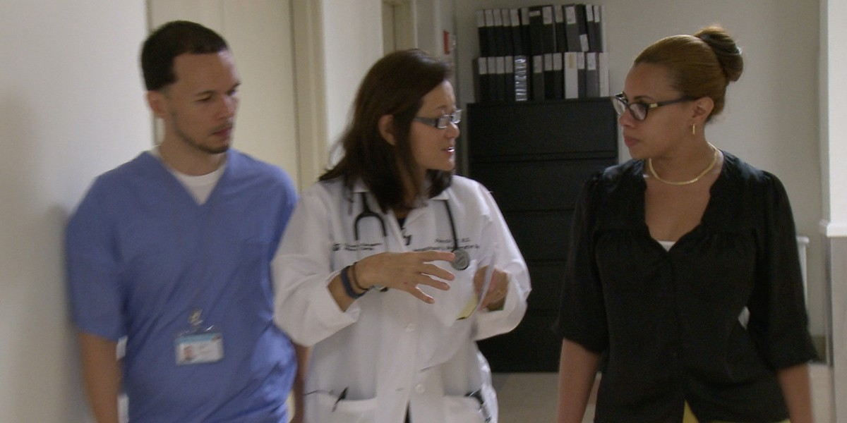 Dr. Tan walking down a hallway with colleagues