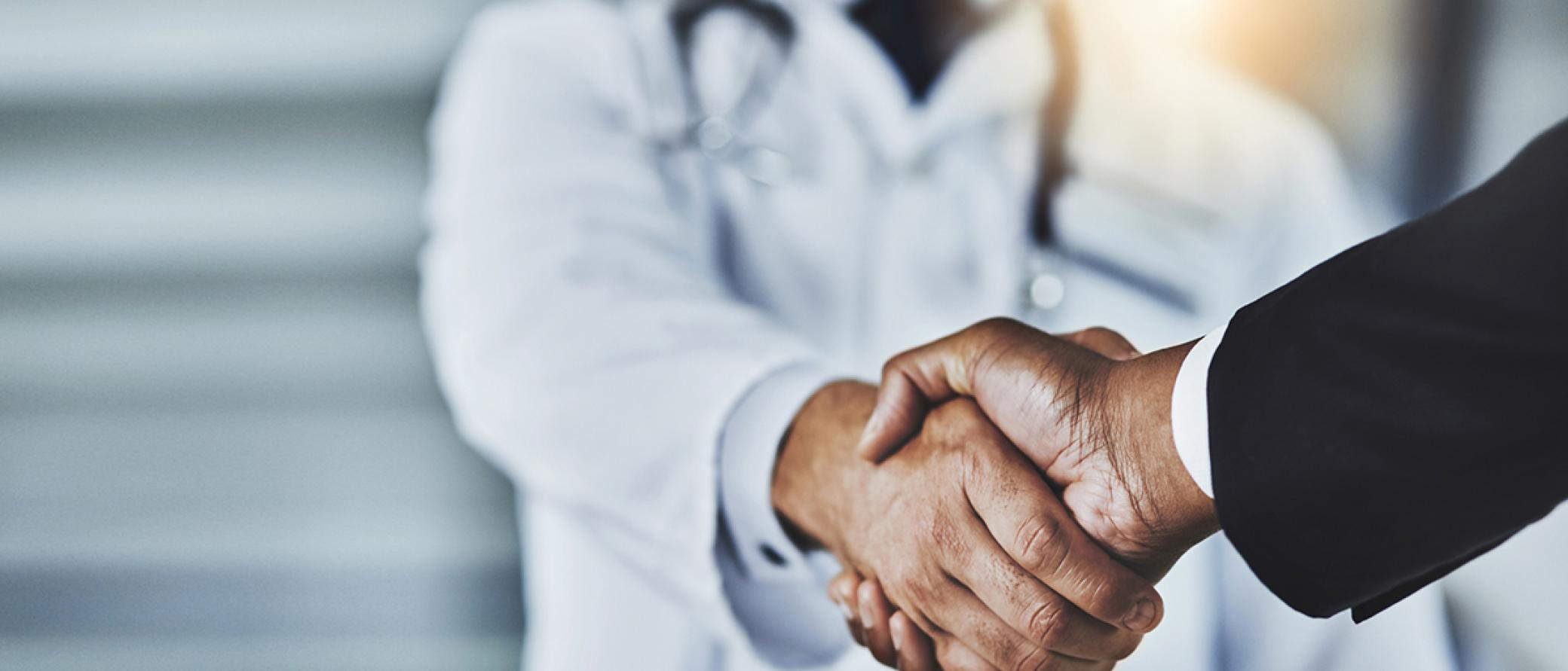 Doctor in white coat shaking hand with a potential hire in business suit