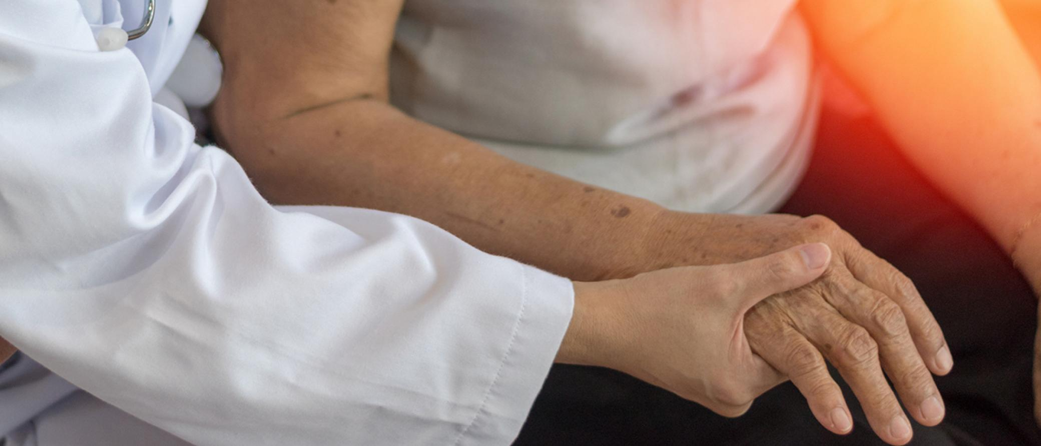 Doctor is holding elderly lady's hand